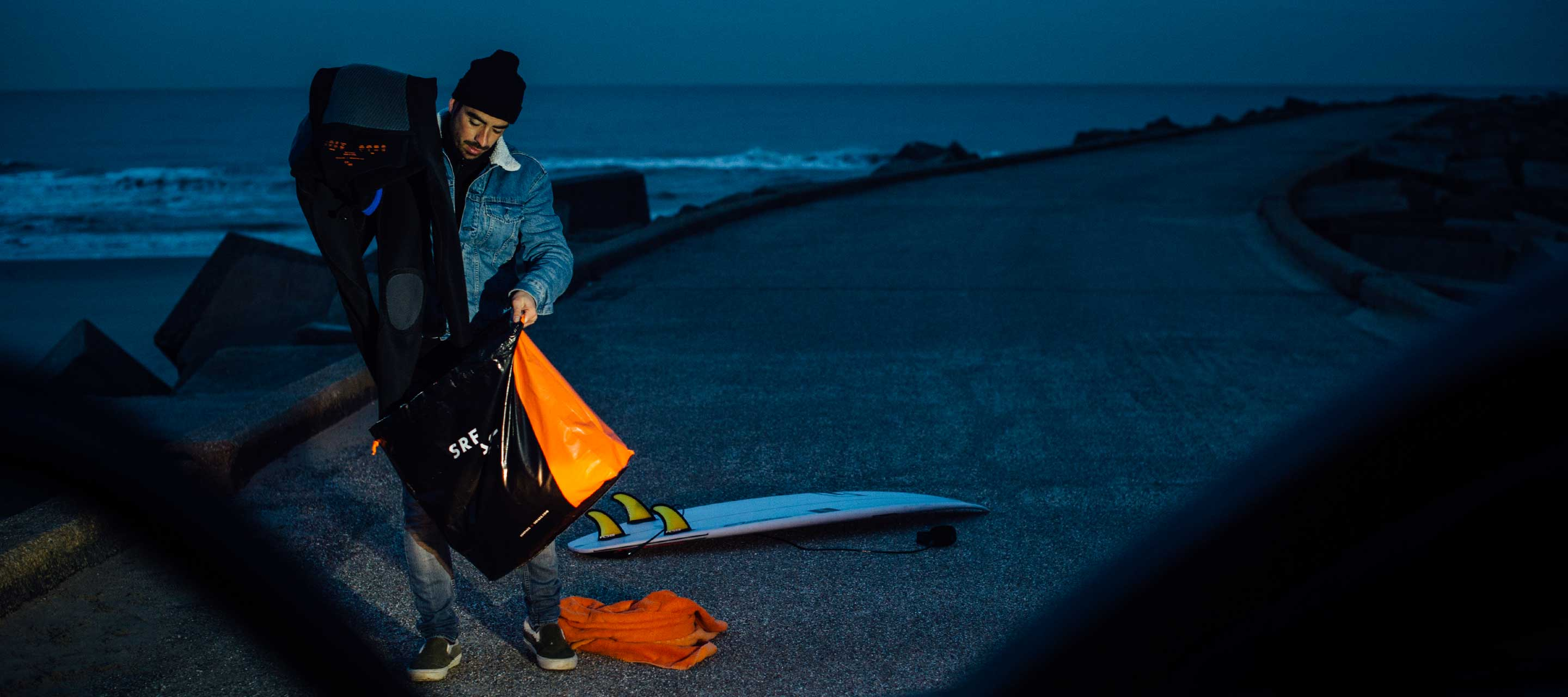 Surfer storing his wetsuit in the SRFACE wetsuit bag