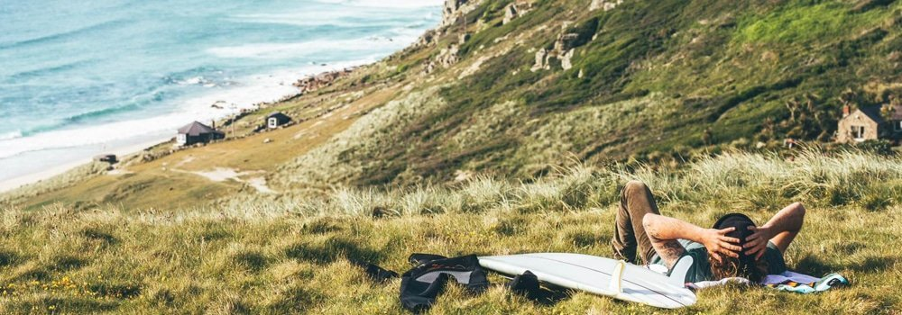 Surfer chilling on hill overlooking surf in cornwall with SRFACE wetsuit