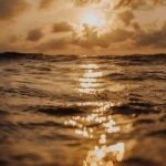 reflective sunset over the ocean water surface with waves